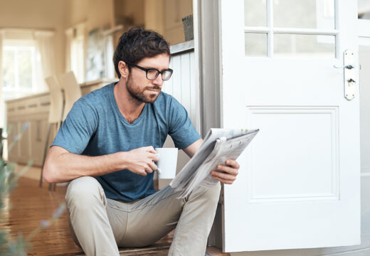 Cropped shot of a handsome young man enjoying his coffee while reading the morning paper
